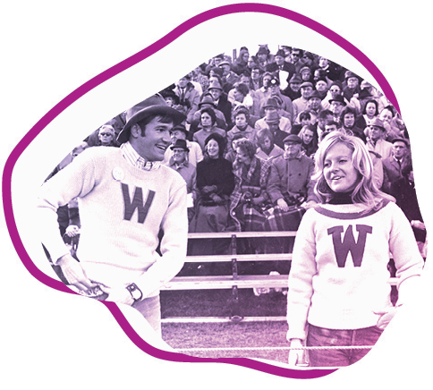men and woman in wearing W sweaters in front of large crowd on bleachers