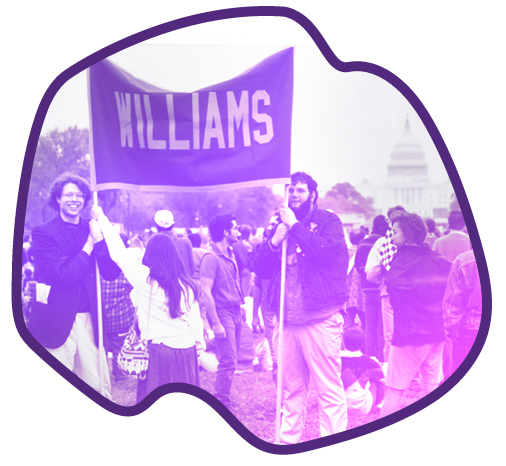 two persons holding a Williams banner with many people in the background