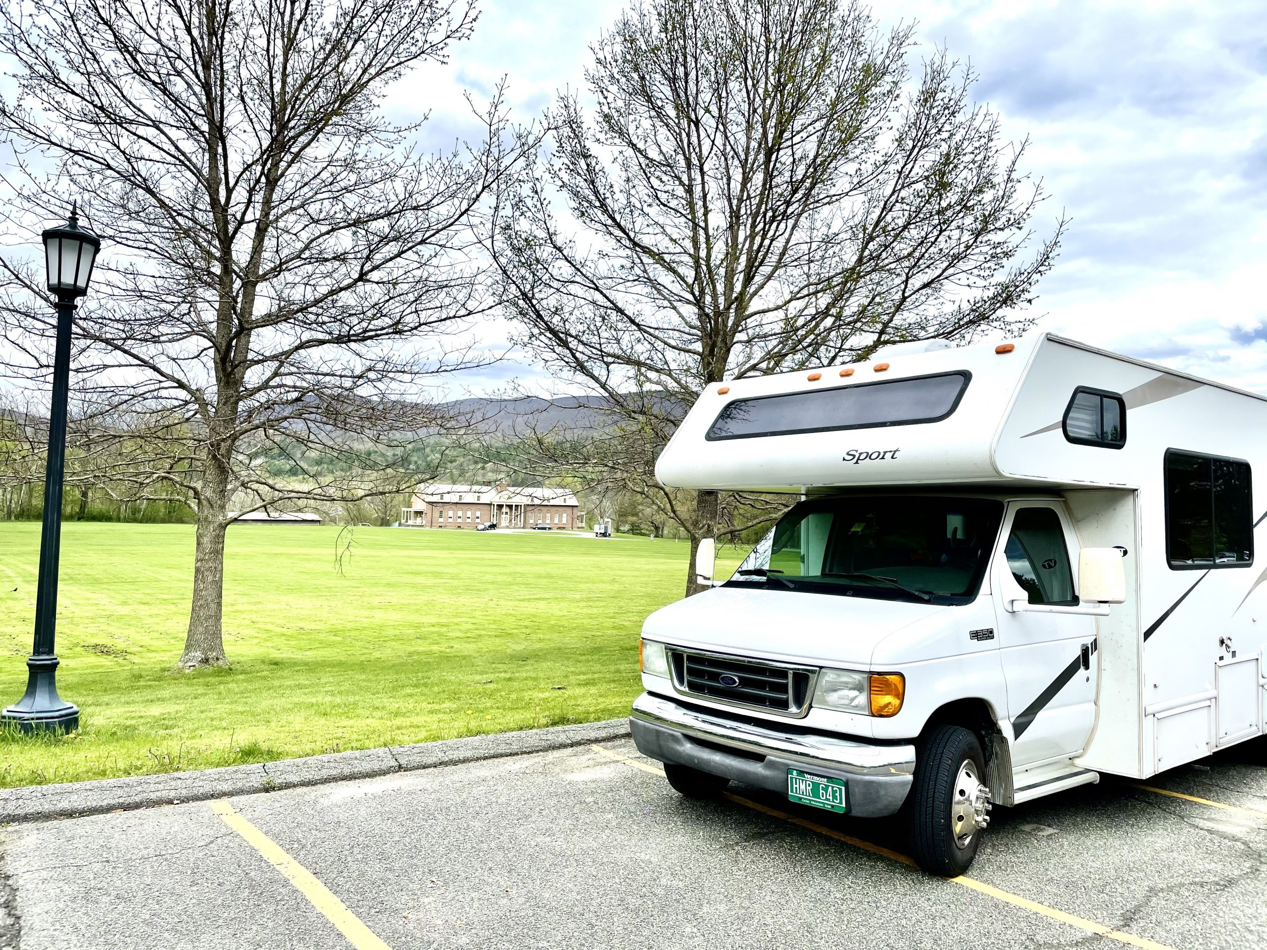 photo of an RV parked next to a field with a lamp post on the left