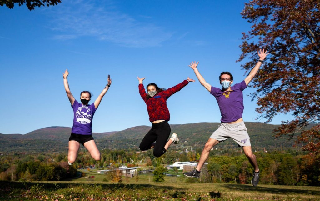 Three students wearing masks are mid-air as they jump in front of a valley view.
