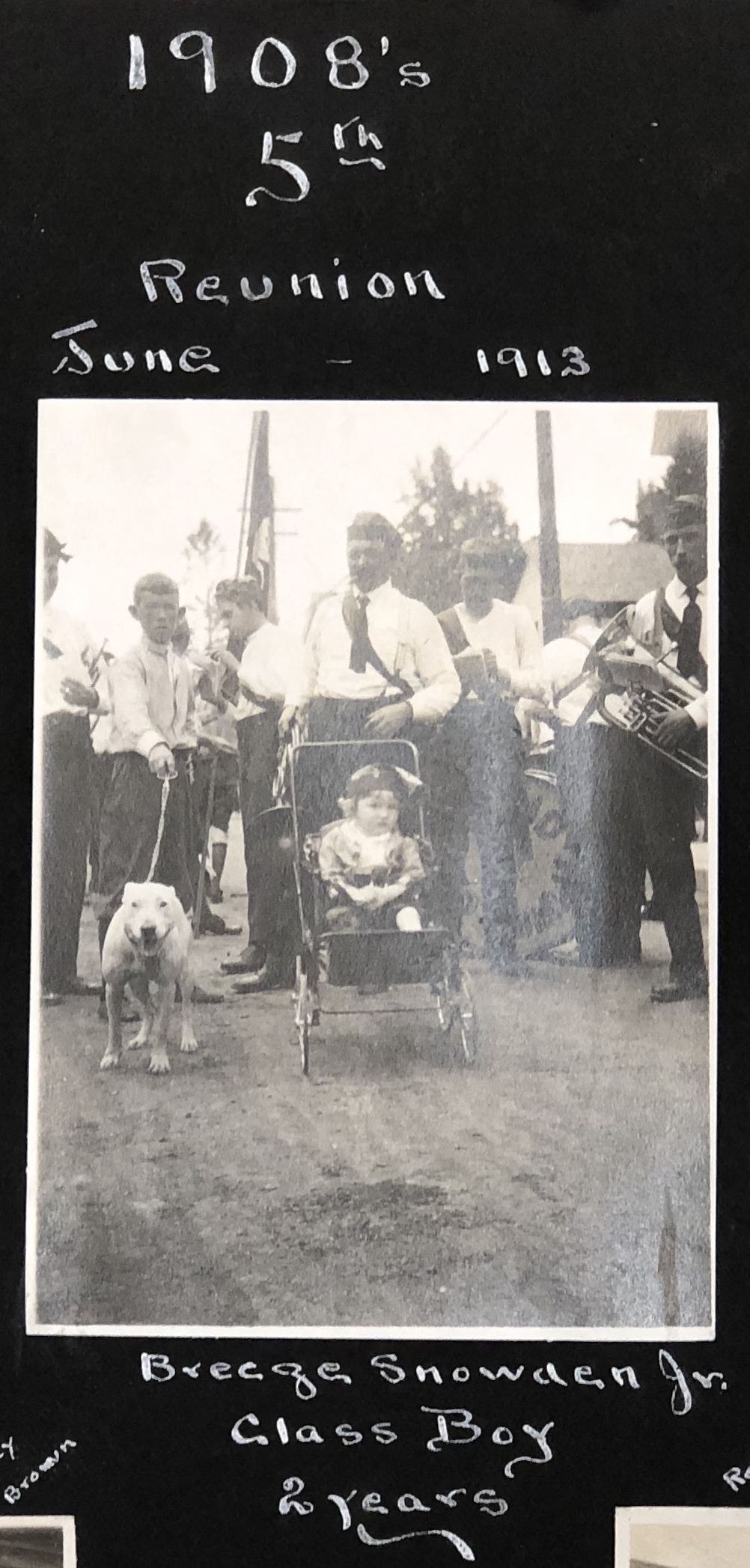 A black and white photography in an album shows a young boy in a stroller with the class of 1908 at their five-year reunion.