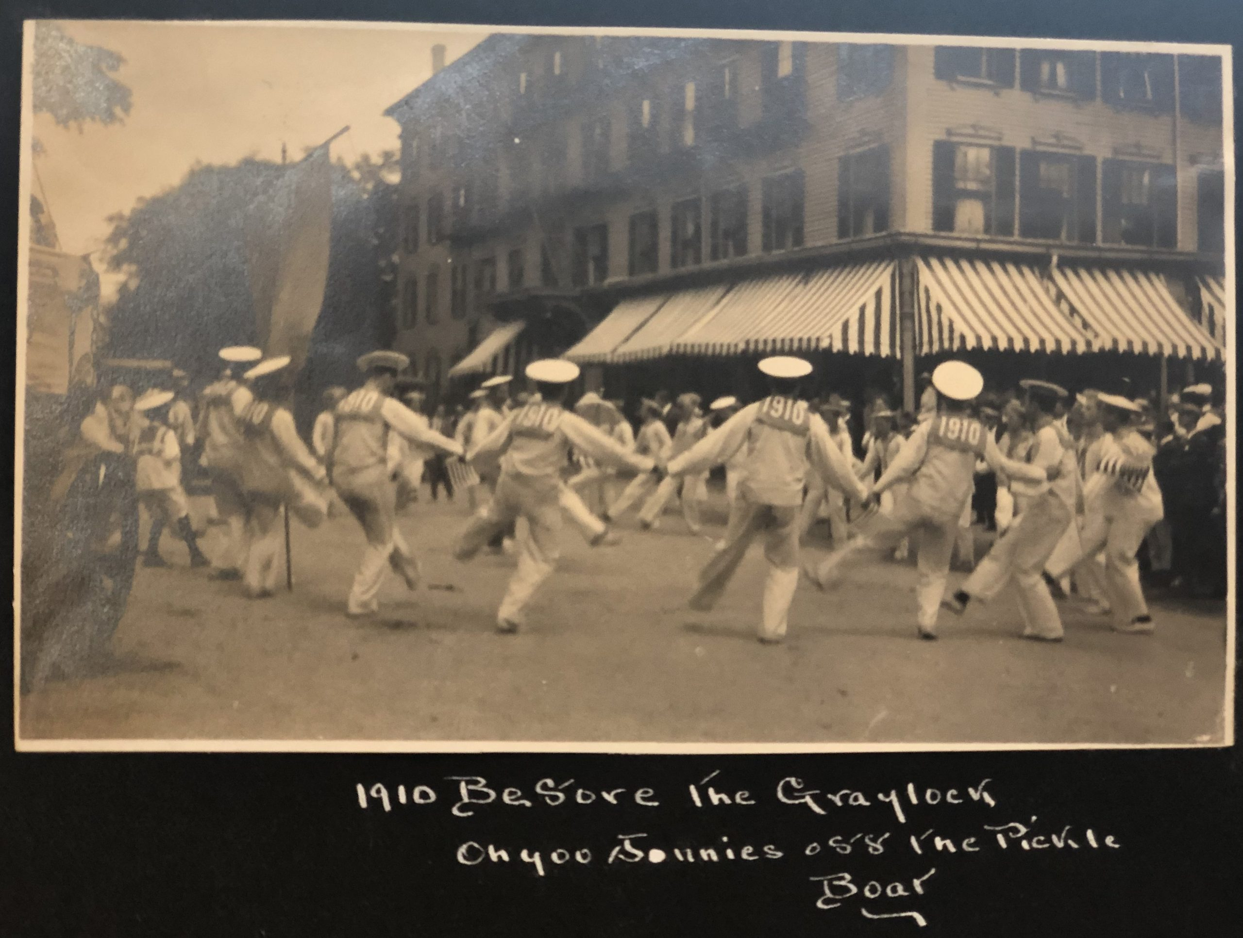 A black and white photograph in an album shows men from the class of 1910 dressed as sailors with dancing in the street at their three-year reunion.