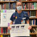 person wearing a mask and eyeglasses in a blue apron, holding a sign with cutout cows and text that reads as 'one step closer to herd immooooooonity!!!.' There is a bookshelf full of books in the background.
