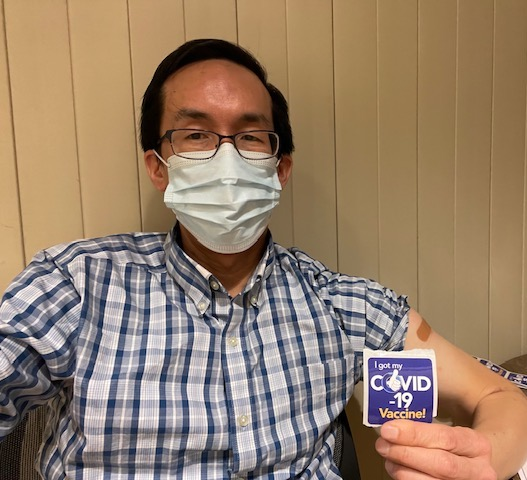 a person sitting down wearing a face mask and holding a sticker that reads