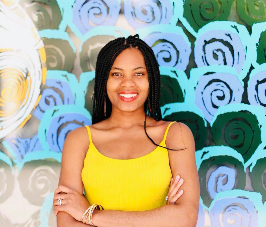 a person wearing a yellow top with long braided hair and a background with abstract circular green and aqua blue patterns