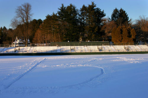 Photograph of Amherst football field covered in snow with B+ stomped into snow