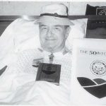 Man in hat propped up in bed with 50th Reunion paraphernalia on his chest