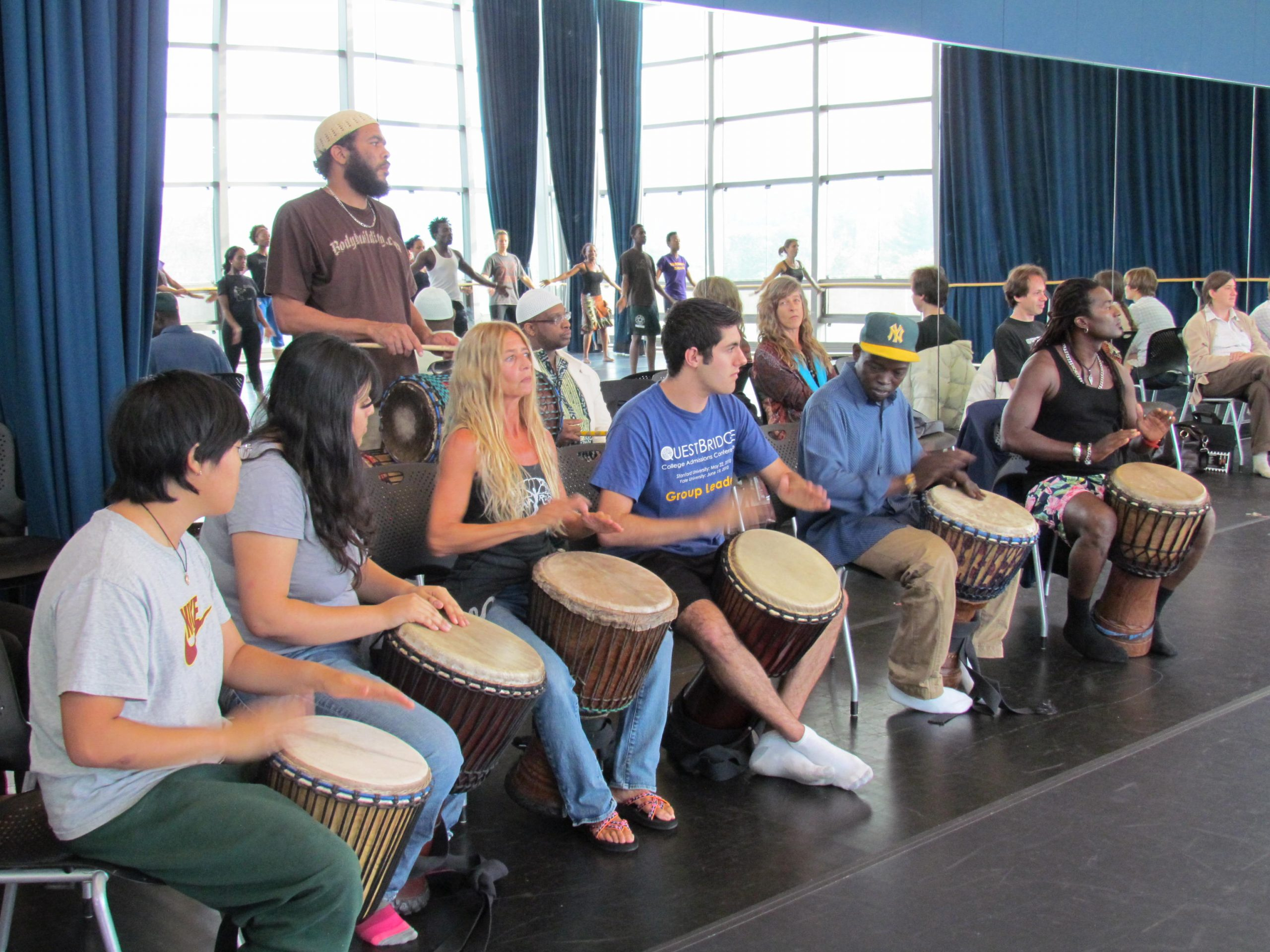 A row of people drumming in front of a mirrored wall
