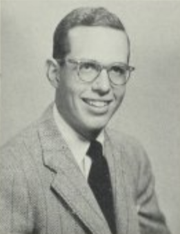 Black and White headshot of a man in glasses and a suit and tie