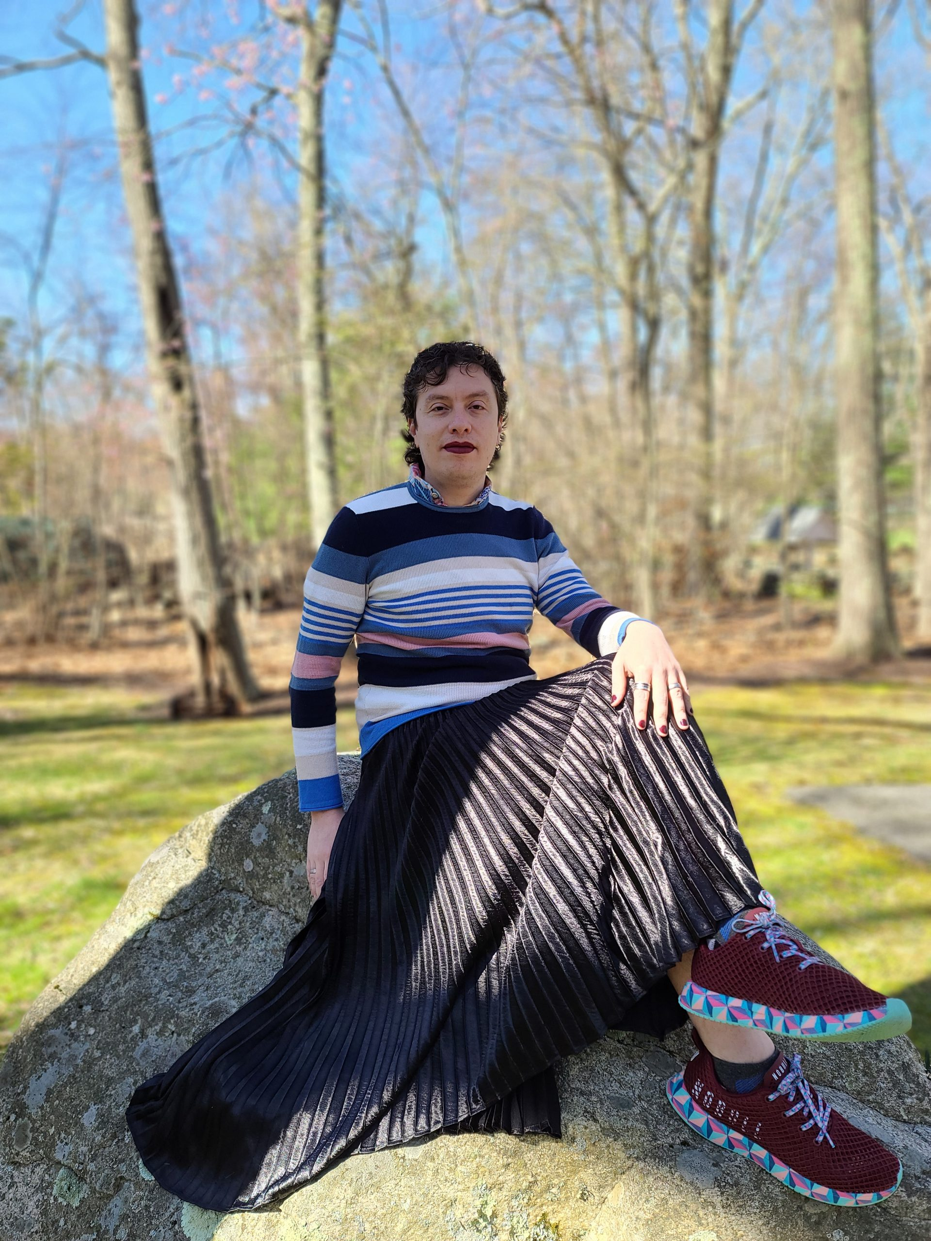 photograph of a person sitting on top of a rock. they are wearing a horizontal striped to in assorted colors, a black skirt, and maroon shoes with a multicolored edge.