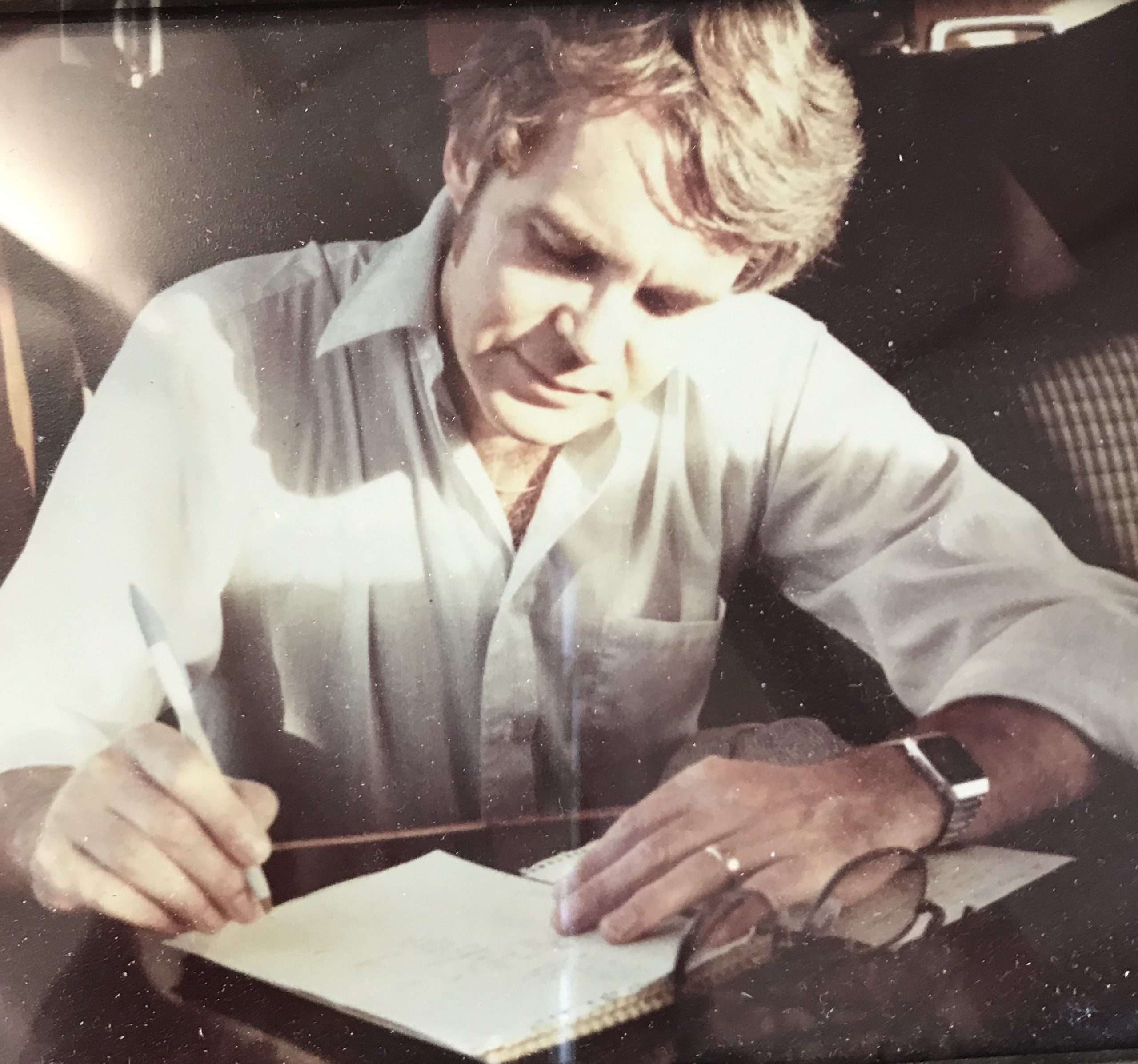Man leaning over writing page with pen in hand