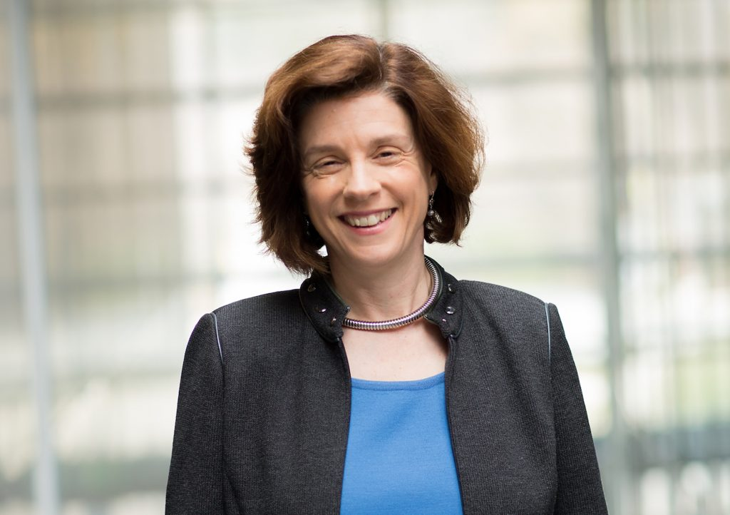 President Maud Mandel smiling, wearing a black blazer and blue top