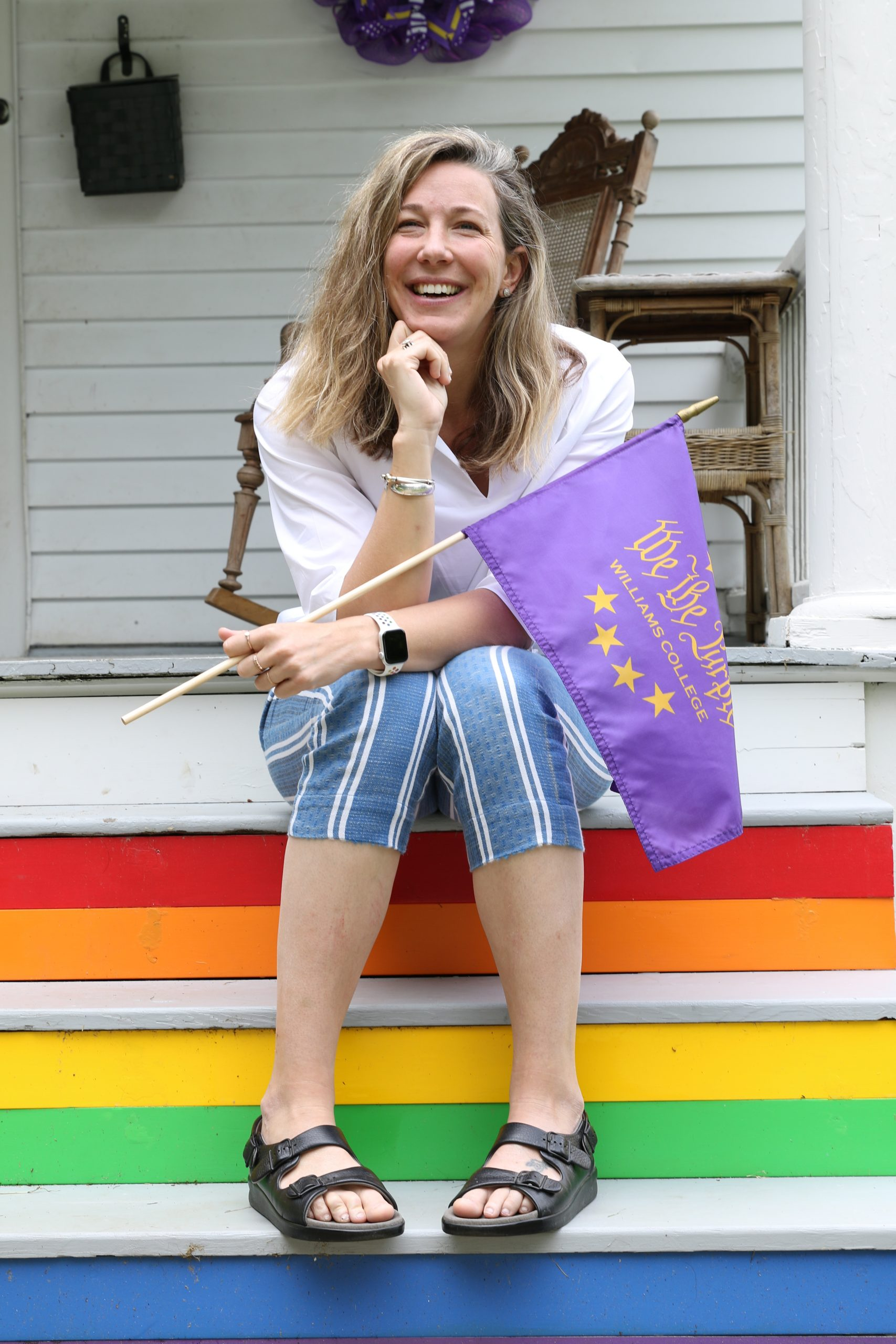 photo of a woman sitting on stairs painted with rainbow colors and holding a purple flag. She is wearing blue striped short pants, a white top, wedges, and has blond hair.