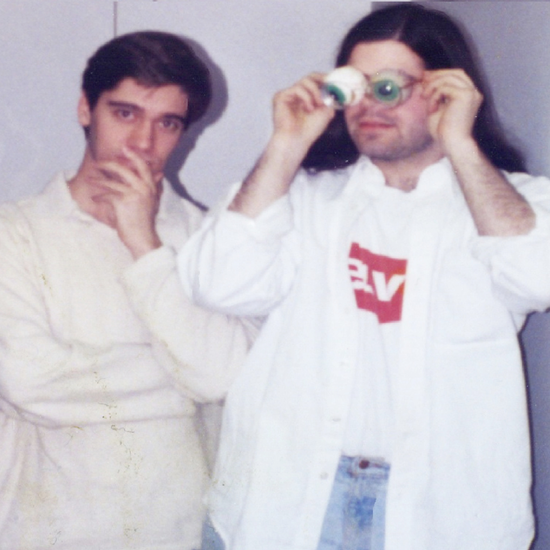 a photo of two persons playing funny poses. person on the left is wearing a white sweater and posing on a thinking pose while person on the right is wearing a white shirt that is open and wearing googly eyes