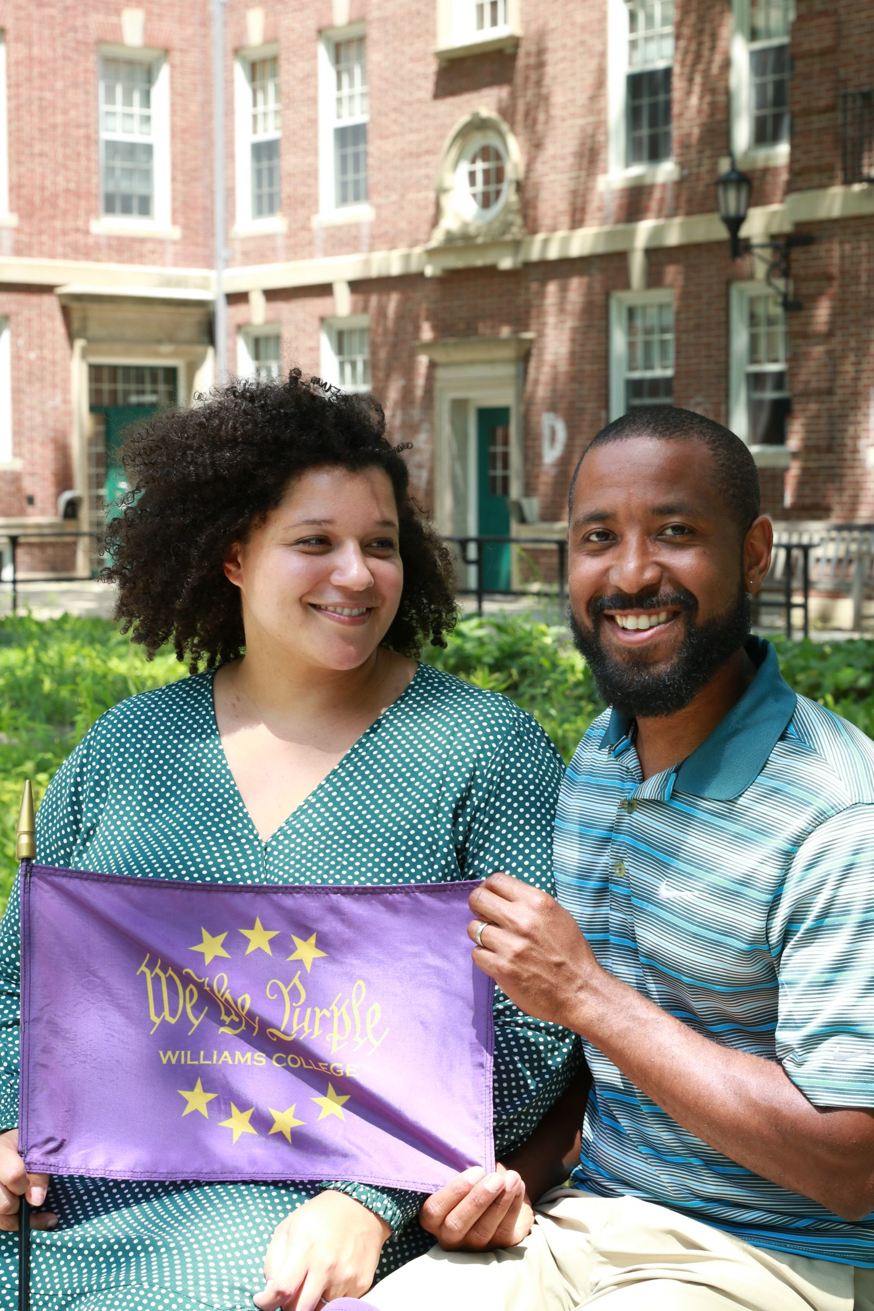 Twink and Markus holding 'We the Purple' flag while sitting in front of Williams Hall.