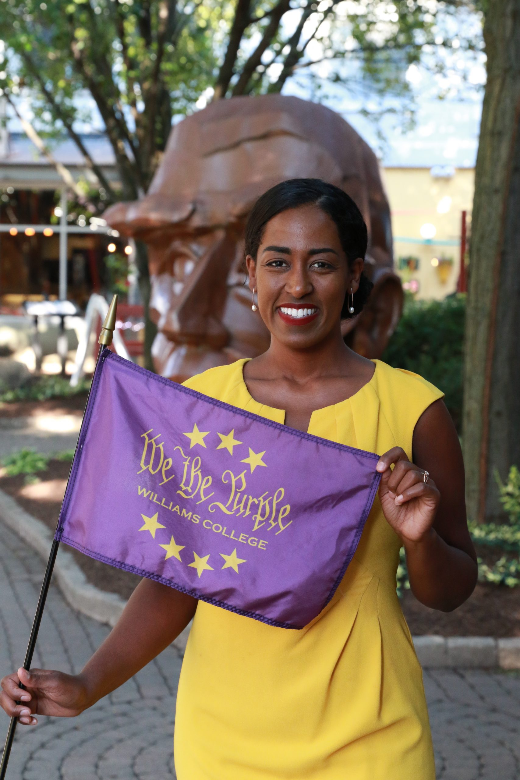 Senator Brouk poses for a photo holding a purple 'We the Purple flag in front of a head sculpture. She is wearing a yellow dress.