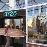 Man holding surfboard outside shop