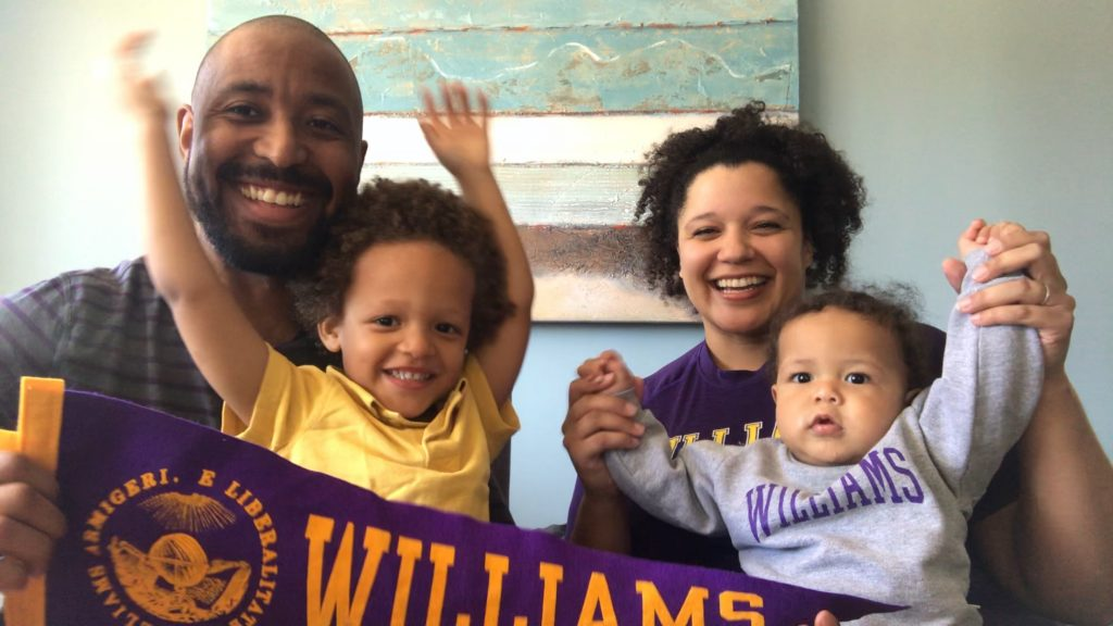 Markus and Twink with their children sitting down while holding a Williams pennant and holding their hands up.