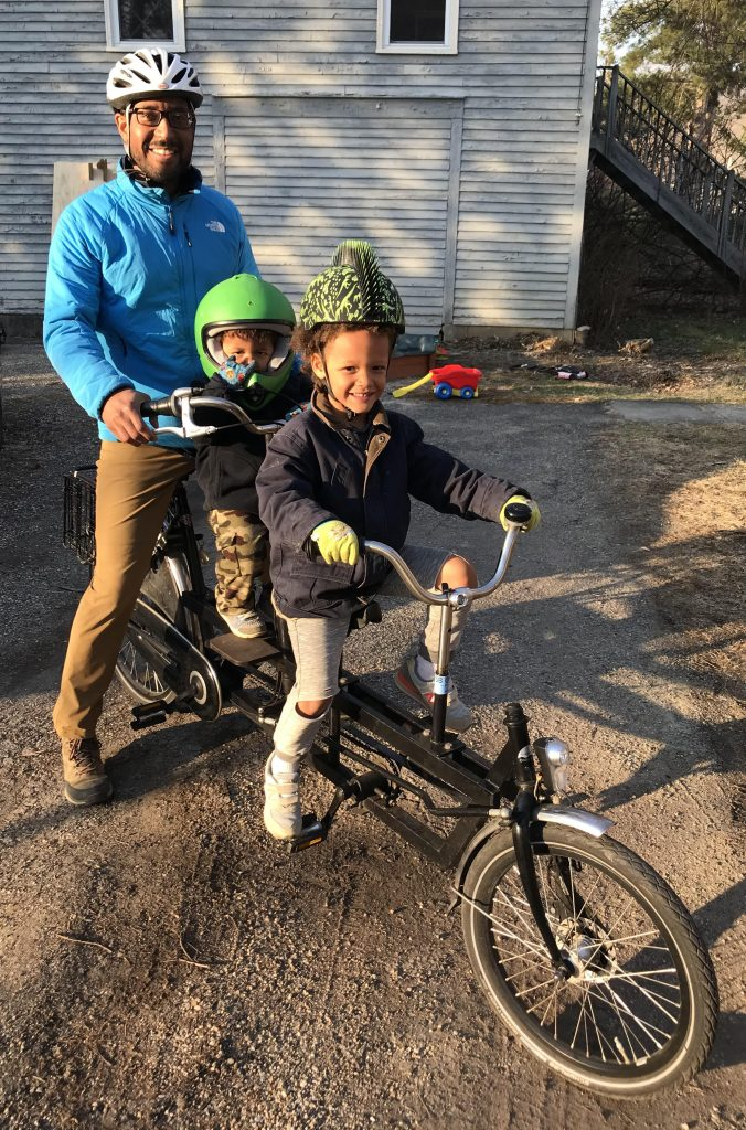 Markus riding a bike with his two children in a tandem bike, wearing helmets.