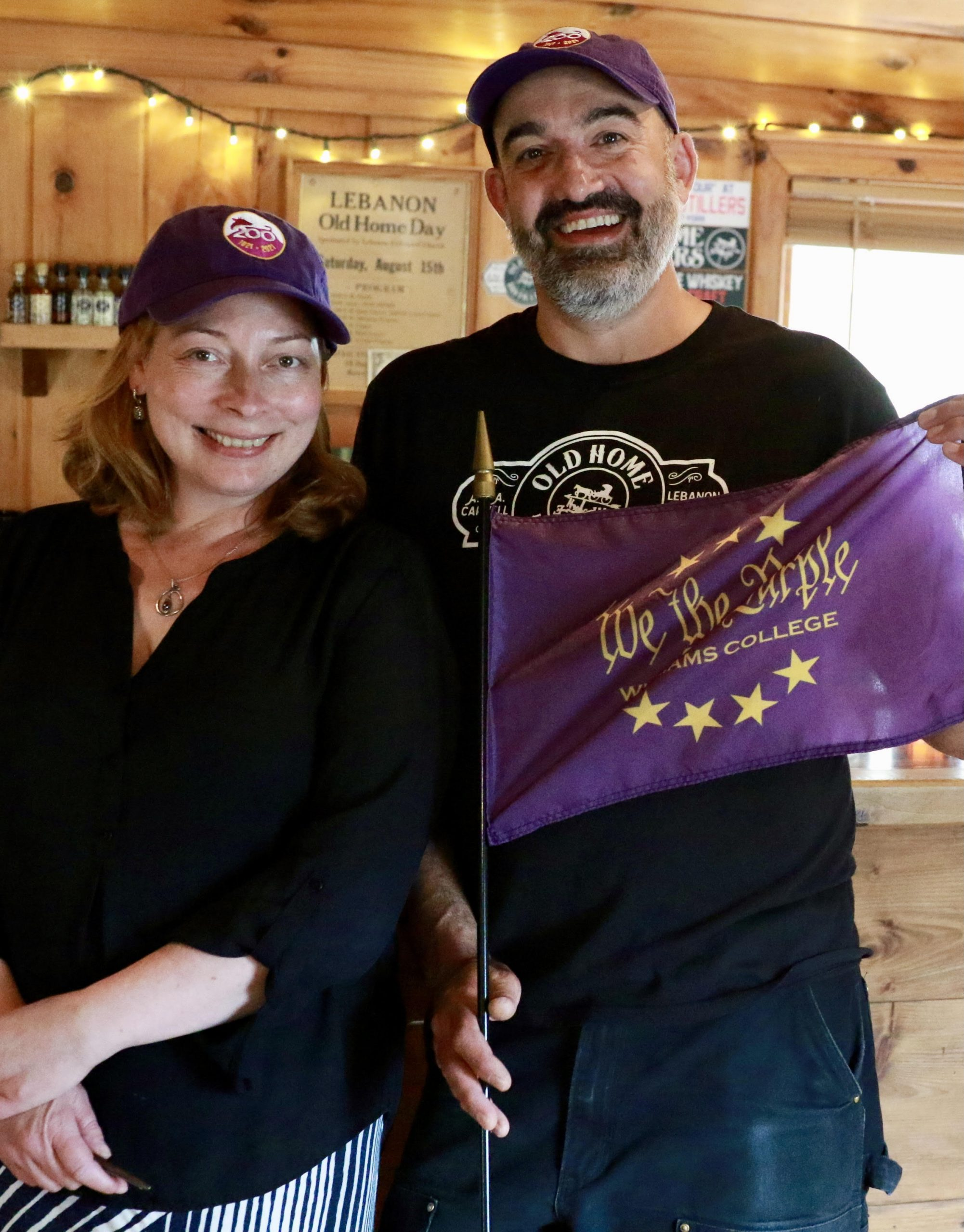 Aaron and his wife, Jasmine, posing for a photo inside Old Home Distillers' tasting room. Jasmine is standing to the left of Aaron and is wearing a black top with a purple Williams bicentennial baseball cap, with her hands crosses. Aaron is standing to Jasmine's right while holding a 'We the Purple' purple flag and wearing a black Old Home Distillers branded shirt and a Williams bicentennial baseball cap.