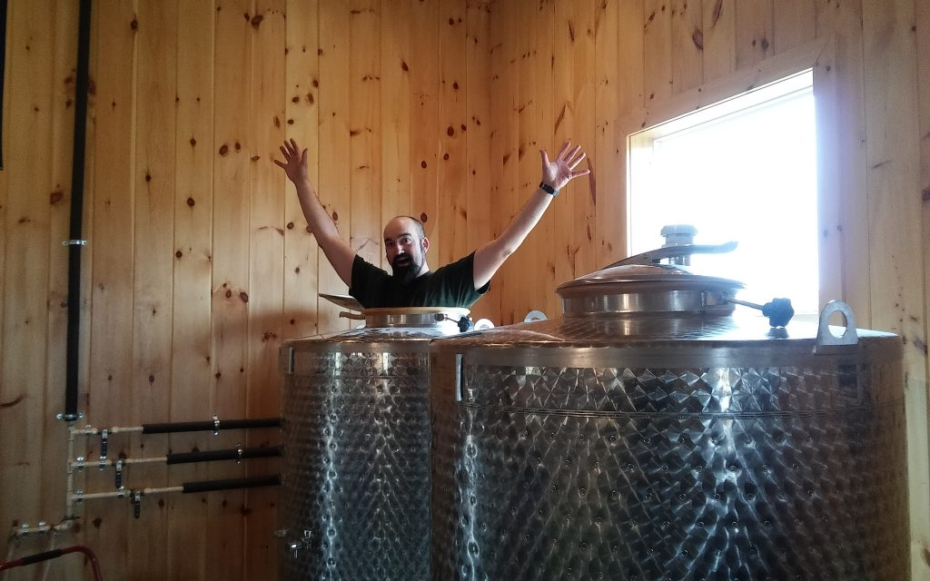 Aaron emerges from behind storage tanks at the distillery.