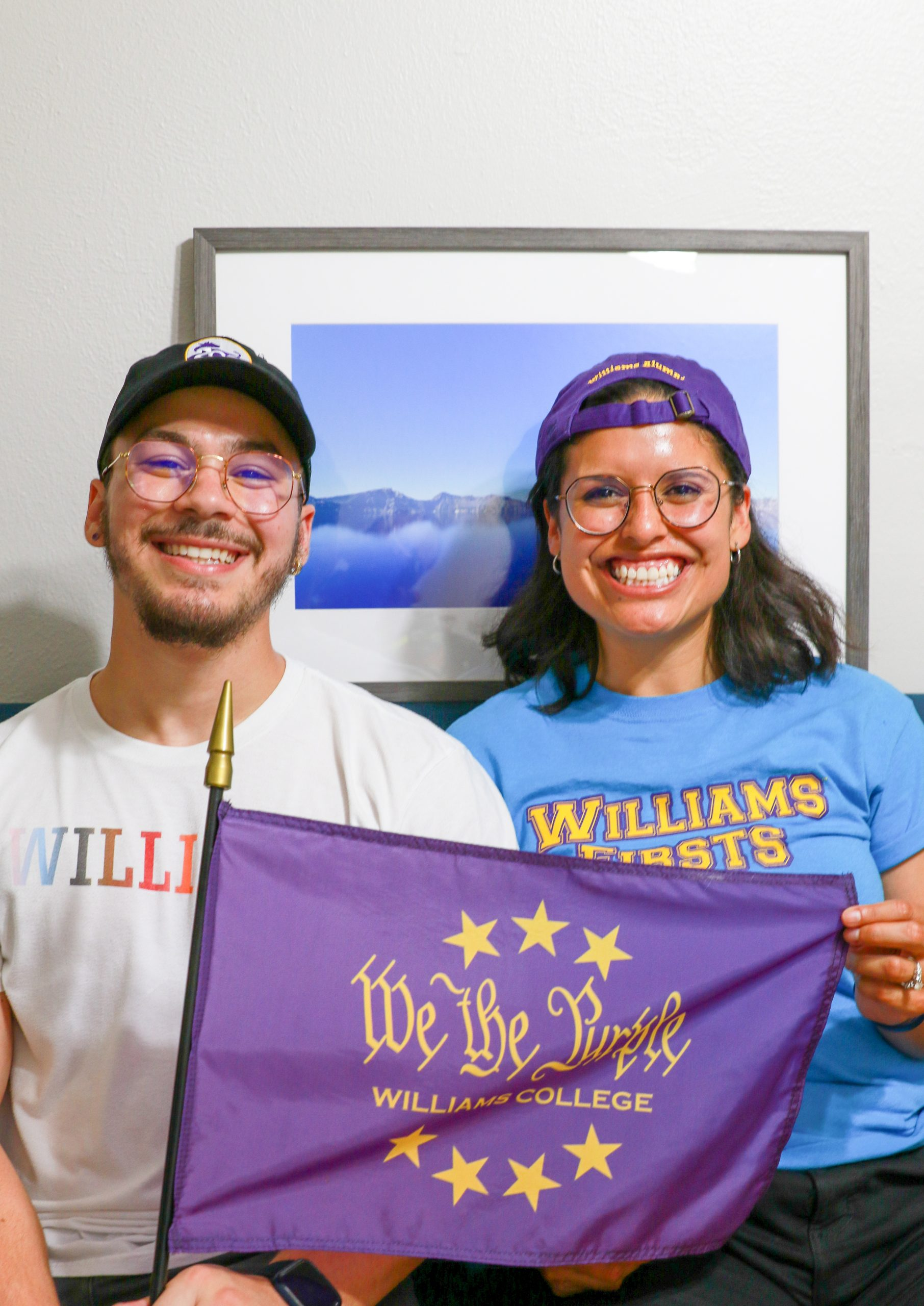 A portrait photograph of Kevin and Alejandra sitting down on a couch, holding a purple 'We the Purple' flag, with a frame of a landscape photo of a lake in the background. Kevin is on the left wearing a black baseball cap with a logo of the bicentennial cow 200th and is wearing a white shirt that has Williams in pride colors. Alejandra is sitting to the right wearing a purple baseball cap backwards and is wearing a blue shirt that reads with yellow text as Williams Firsts.