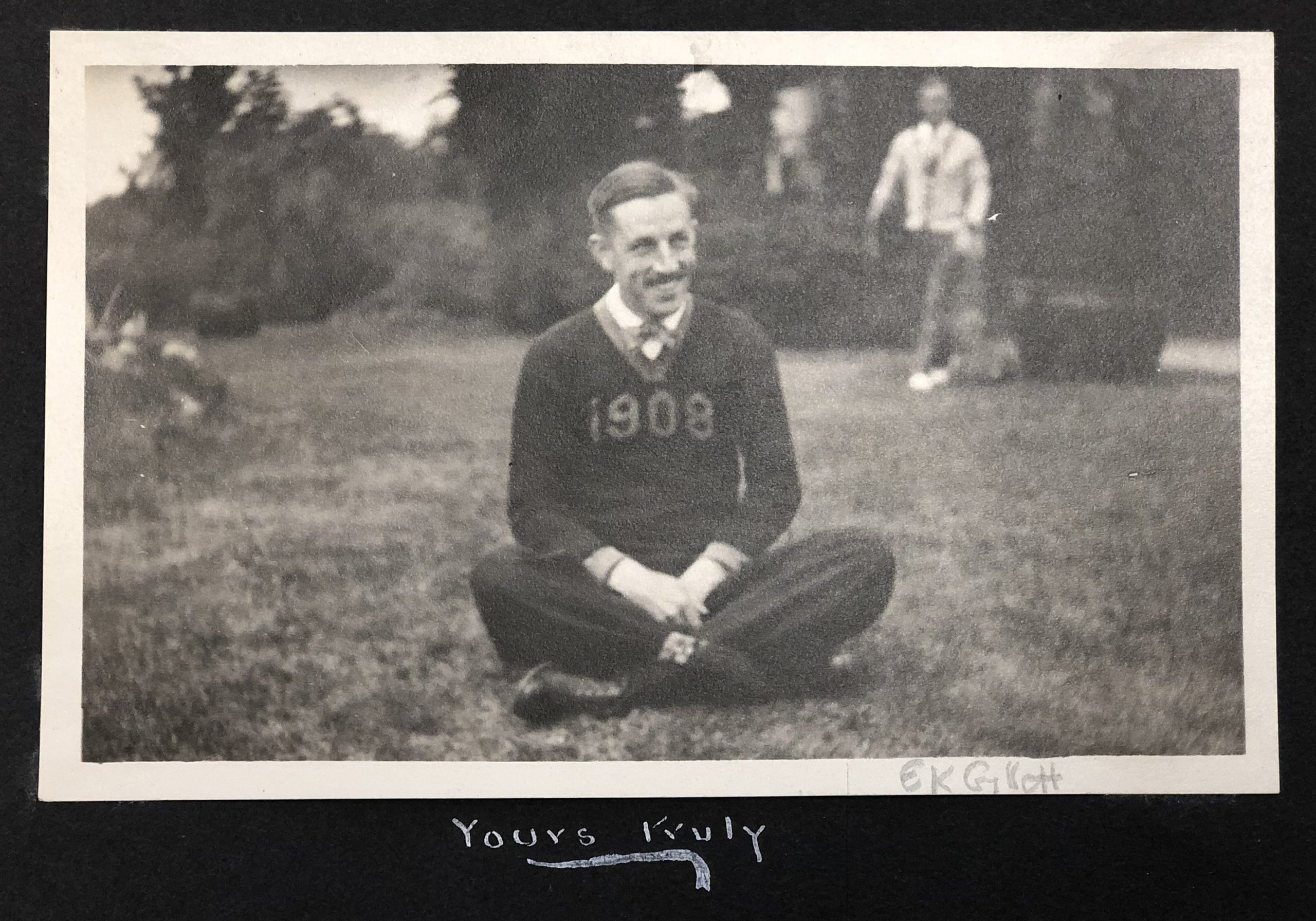 An archival black-and-white photography of E. Kendall Gillet, who wears a sweater with the year 1908 across the chest.