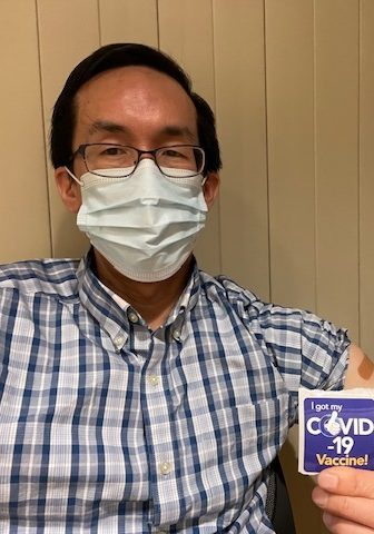"""a person sitting down wearing a face mask and holding a sticker that reads """"I got my Covid-19 Vaccine!"""""""