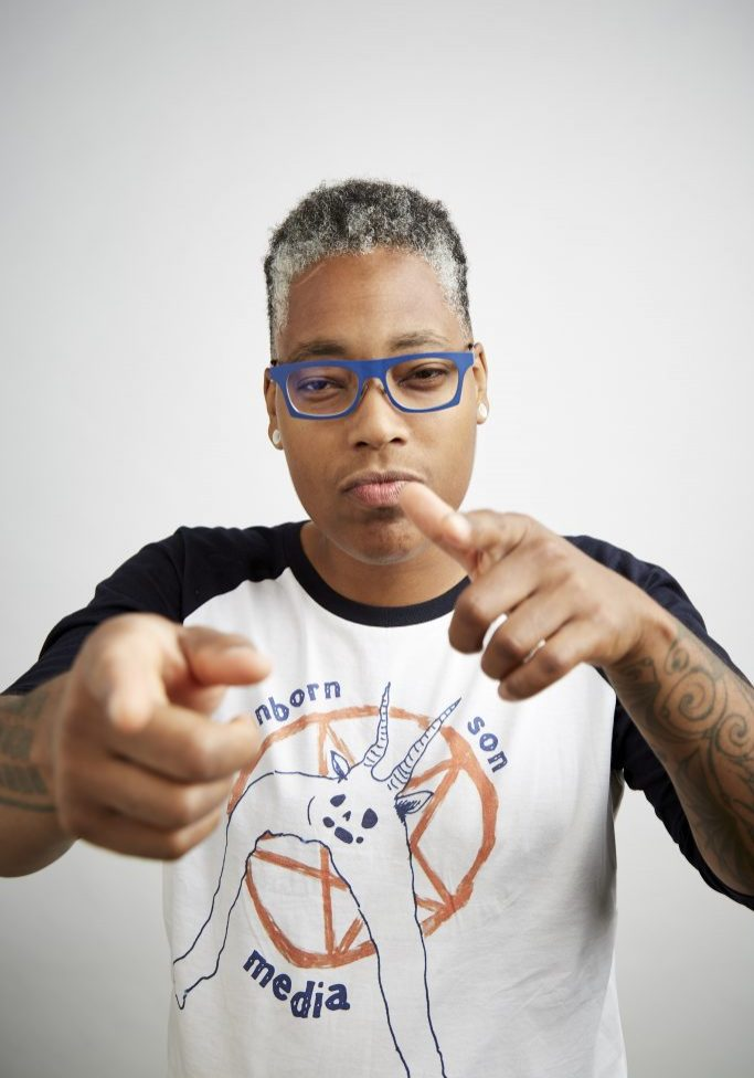 saifa flex and pointing straight ahead, wearing glasses and a shirt with words that say 'unborn, son, media.'
