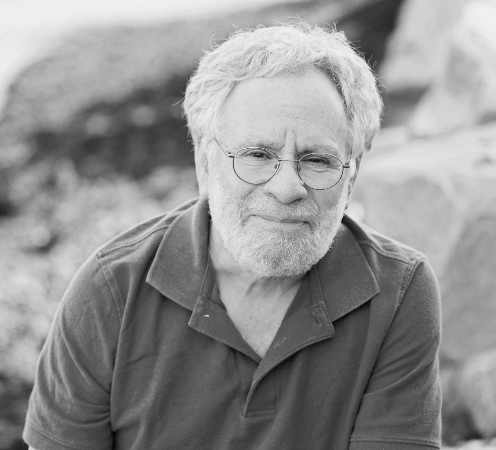 black and white photo with person wearing glasses and polo shirt.